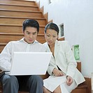 Businessman and businesswoman sitting on a staircase and looking at a laptop (thumbnail)