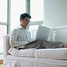 Young man sitting on a couch using a laptop