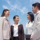 Low angle view of a businessman talking to three businesswomen (thumbnail)