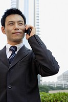 Businessman conversing on a cellphone, portrait (thumbnail)