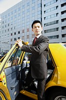 Businessman stepping out of a car (thumbnail)