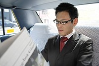 Businessman reading a newspaper in a car, portrait