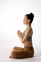 Side view of a young woman meditating in lotus position