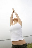View of a young woman stretching out her hands towards the sky