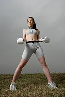 View of a young woman standing with boxing gloves