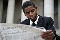 Portrait of young business man reading newspaper, Cape Town, Western Cape Province, South Africa