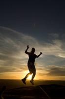 Silhouetted tourist jumping at Ngoma Kurira, Mashonaland East Province, Zimbabwe