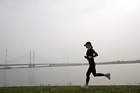 View of a young woman jogging beside a river