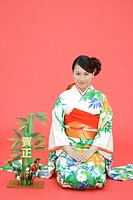 View of teenage girl in traditional outfit beside a plant