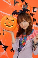 Portrait of teenage girl holding jack-o-lantern (thumbnail)