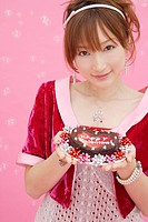 Portrait of a teenage girl holding a cake (thumbnail)