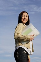 View of a young woman standing with a folder in her hand (thumbnail)