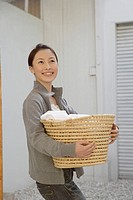 Side view of a young woman holding a basket
