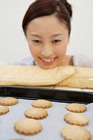 A young woman looking at the tray of biscuits