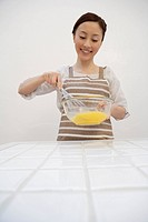 View of a young woman mixing egg yolks with whisk