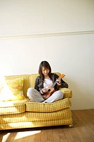View of a young woman playing guitar
