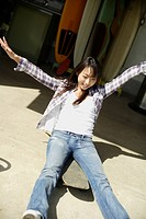 View of a young woman sitting on the skateboard with arms outstretched