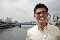 A smiling young man standing with river in background (thumbnail)