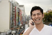 A young man using cellphone with buildings in background