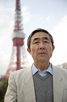 A senior man standing with a tower in background