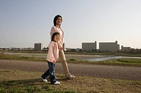 Side view of a mother and daughter walking on pathway