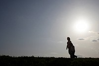 Silhouette of a mother and daughter walking