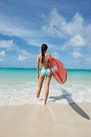 A woman standing on beach with surfboard in hand