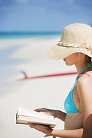 A woman reading book on beach (thumbnail)