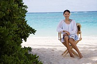 A woman sitting on chair on beach