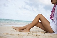 Low section of a woman sitting at beach