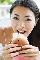 Portrait of a young woman eating burger (thumbnail)
