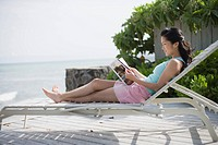 A woman reading book on deck chair (thumbnail)