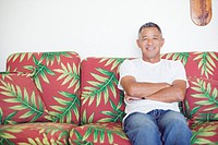 Mature man sitting on sofa (thumbnail)