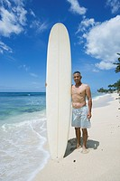 Mature man standing with surfboard on beach