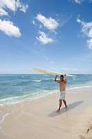 Mature man walking with surfboard