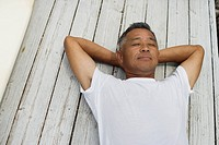 Mature man sleeping on planks