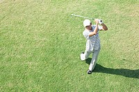 Elevated view of mature a man holding golf club
