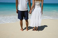 Lo section of a couple holding hands at beach