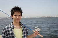 Portrait of a young man holding a fishing rod (thumbnail)