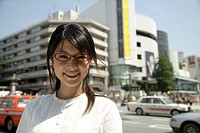 Portrait of a young woman smiling with buildings in background