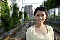 Portrait of a young woman with railway track in background