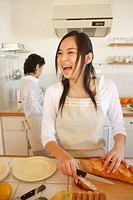 Teenage girl 14_15 with knife in kitchen while senior women in background