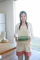 Teenage girl 14_15 holding stack of plates, portrait