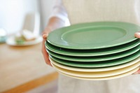 Teenage girl 14_15 holding stack of plates