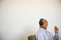 Senior man listening music, side view (thumbnail)