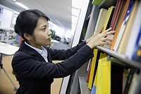 A woman looks over the shelf containing various files