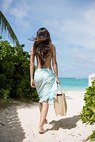 Rear view of a woman walking at beach