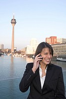 Young business woman talking on mobile phone, in front of city skyline, television tower, Zollhof, Media Harbour, architecture of Frank O.Gehry, Duess...