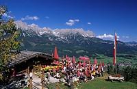hikers on terrace of alpine hut Ruebezahlalm, view to Wilder Kaiser range, Hartkaser, Ellmau, Tyrol, Austria