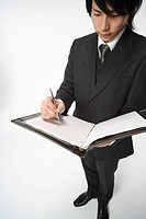 Young man writing in file